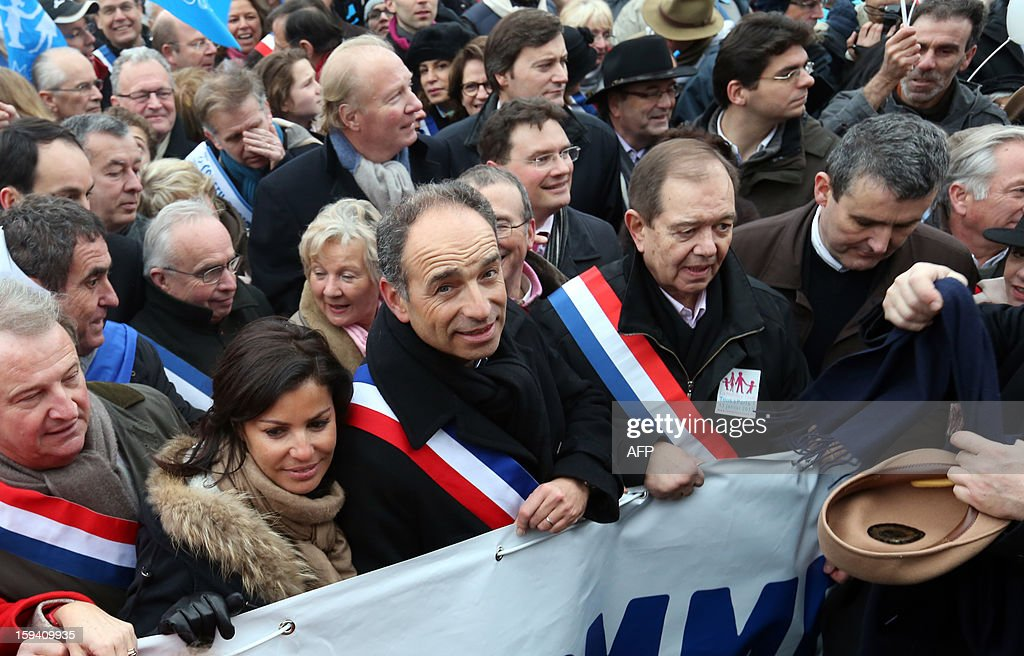 French UMP opposition right-wing party president Jean-Francois Cope (3rdL) and his wife Nadia Hamama (2ndL), UMP member of parliament Patrick Ollier (2ndR) take part in a protest against same-sex marriage on January 13, 2013 in Paris. Tens of thousands march in Paris on January 13 to denounce government plans to legalise same-sex marriage and adoption which have angered many Catholics and Muslims, France's two main faiths, as well as the right-wing opposition. The French parliament is to debate the bill -- one of the key electoral pledges of Socialist President -- at the end of this month. AFP PHOTO / THOMAS SAMSON