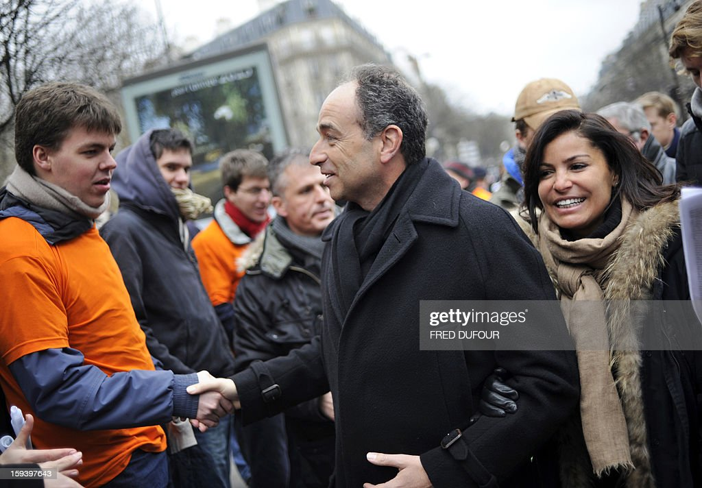 French UMP opposition right-wing party president Jean-Francois Cope, flanked by his wife Nadia Hamama (R), shakes hands with a demonstrator as he takes part in a march against same-sex marriage on January 13, 2013 in Paris. Tens of thousands march in Paris on January 13 to denounce government plans to legalise same-sex marriage and adoption which have angered many Catholics and Muslims, France's two main faiths, as well as the right-wing opposition. The French parliament is to debate the bill -- one of the key electoral pledges of Socialist President -- at the end of this month.