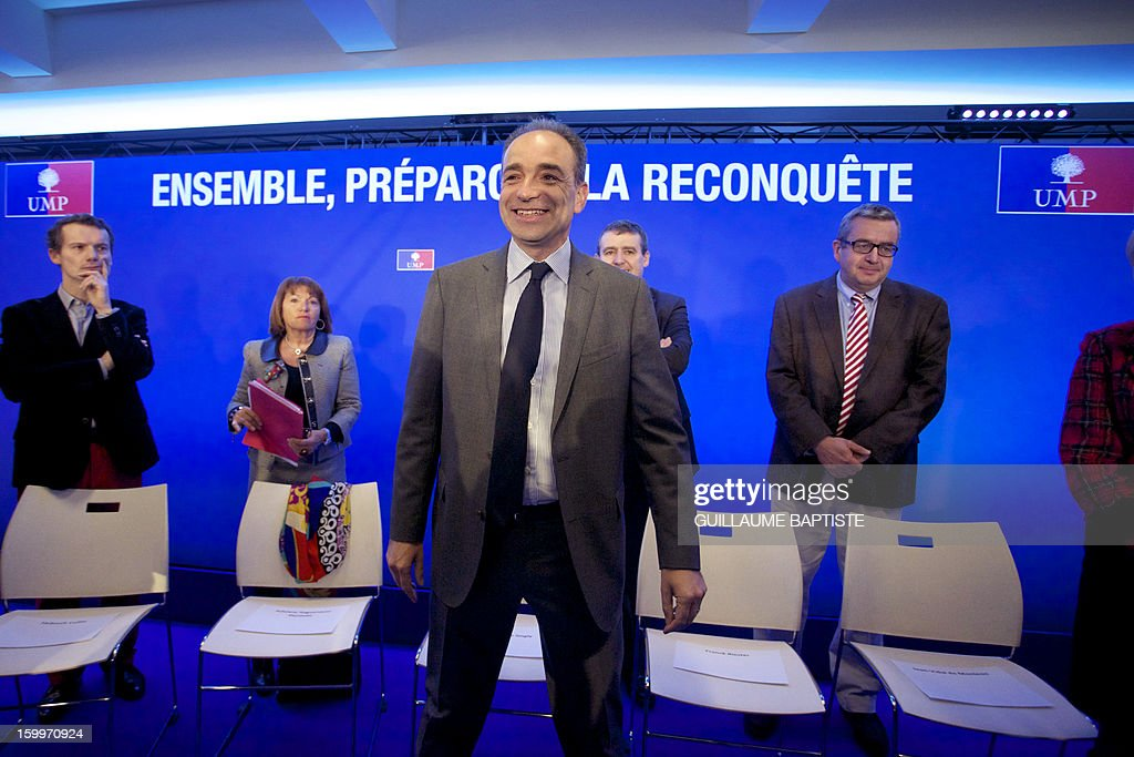 French UMP opposition right-wing party President Jean-Francois Cope (C) arrives to deliver a speech on January 24, 2013 at the party headquarters in Paris, as he takes part in a convention focused on family matters. The board reads : 'Together, let us prepare the reconquest'. AFP PHOTO GUILLAUME BAPTISTE