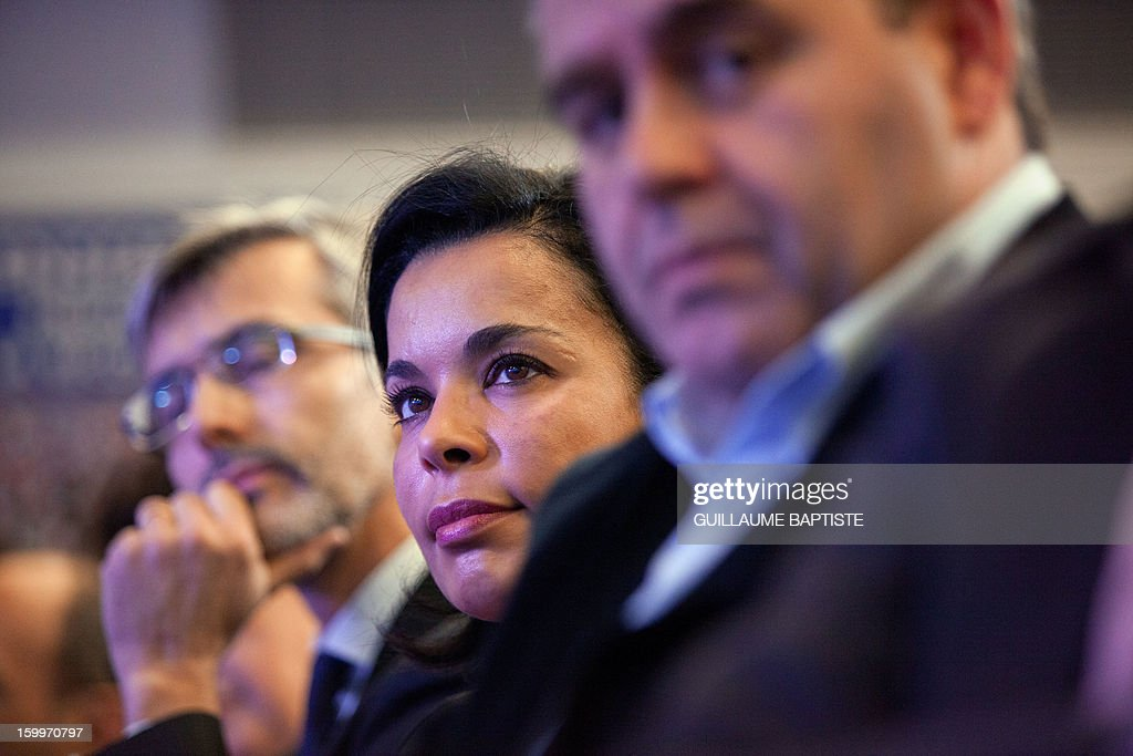 French UMP opposition right-wing party's member, Salima Saa (C) and UMP former Minister Xavier Bertrand (R) listen to speeches, on January 24, 2013 at the party headquarters in Paris, during a convention focused on family matters.