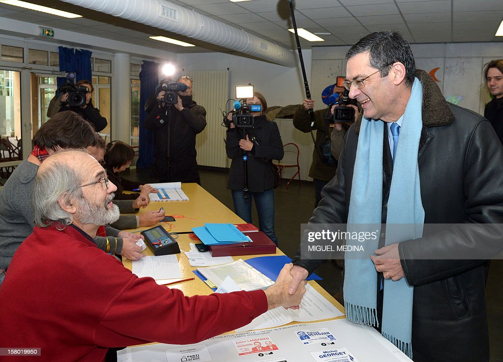 French UMP right-wing party former minister Patrick Devedjian (R), candidate for his reelection as member of Parliament, in the Hauts-de-Seine 13th constituency, shakes hand with a member of a polling station before voting, in Antony, a Paris southern suburb, on December 9, 2012. French Conseil Constitutionnel, one of the country's highest courts, cancelled his precedent election because his substitute was also the one for a senator, which is illegal. MEDINA