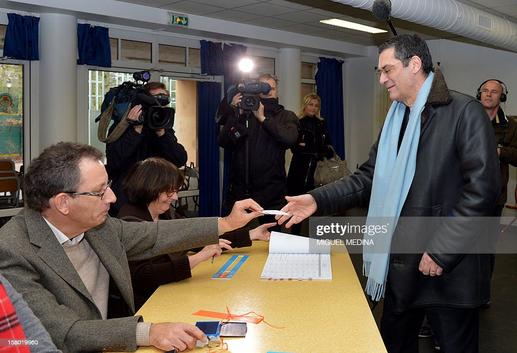 French UMP right-wing party former minister Patrick Devedjian (R), candidate for his reelection as member of Parliament, in the Hauts-de-Seine 13th constituency, prepares to vote in a polling station, in Antony, a Paris southern suburb, on December 9, 2012. French Conseil Constitutionnel, one of the country's highest courts, cancelled his precedent election because his substitute was also the one for a senator, which is illegal. MEDINA
