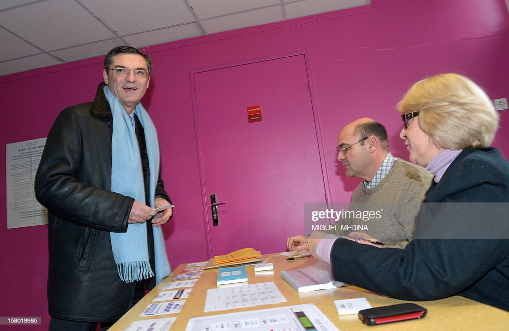 French UMP right-wing party former minister Patrick Devedjian, candidate for his reelection as member of Parliament, in the Hauts-de-Seine 13th constituency, presents his ID card before voting in a polling station, in Antony, a Paris southern suburb, on December 9, 2012. French Conseil Constitutionnel, one of the country's highest courts, cancelled his precedent election because his substitute was also the one for a senator, which is illegal. MEDINA