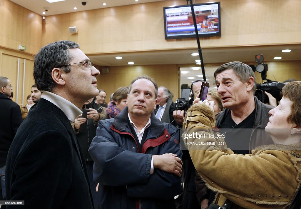 French UMP right-wing party former minister Patrick Devedjian (C), candidate for his reelection as member of Parliament, in the Hauts-de-Seine 13th constituency, looks at the results on a screen as he answers to journalists in Antony town hall, a Paris southern suburb, on December 16, 2012. Devedjian said he considers being reelected after he got nearly 60% of the votes in the two main towns of the district. French Conseil Constitutionnel, one of the country's highest courts, cancelled his precedent election because his substitute was also the one for a senator, which is illegal. GUILLOT