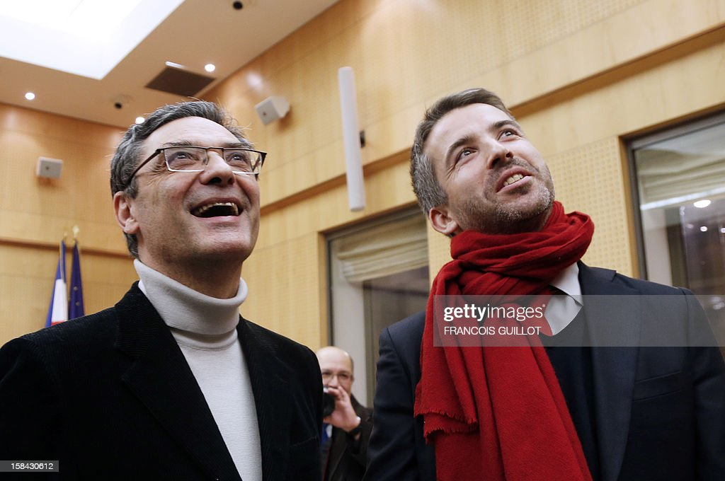 French UMP right-wing party former minister Patrick Devedjian (L), candidate for his reelection as member of Parliament, in the Hauts-de-Seine 13th constituency, smiles as he looks the first results of the second round on a screen with his challenger Julien Landfried from MRC left party, in Antony town hall, a Paris southern suburb, on December 16, 2012. Devedjian said he considers being reelected after he got nearly 60% of the votes in the two main towns of the district. French Conseil Constitutionnel, one of the country's highest courts, cancelled his precedent election because his substitute was also the one for a senator, which is illegal. GUILLOT