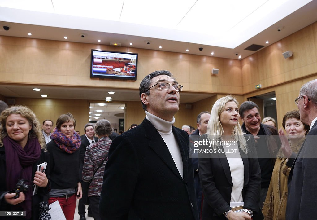 French UMP right-wing party former minister Patrick Devedjian (C), candidate for his reelection as member of Parliament, in the Hauts-de-Seine 13th constituency, looks at the first results of the second round on a screen in Antony town hall, a Paris southern suburb, on December 16, 2012. Devedjian said he considers being reelected after he got nearly 60% of the votes in the two main towns of the district. French Conseil Constitutionnel, one of the country's highest courts, cancelled his precedent election because his substitute was also the one for a senator, which is illegal. GUILLOT
