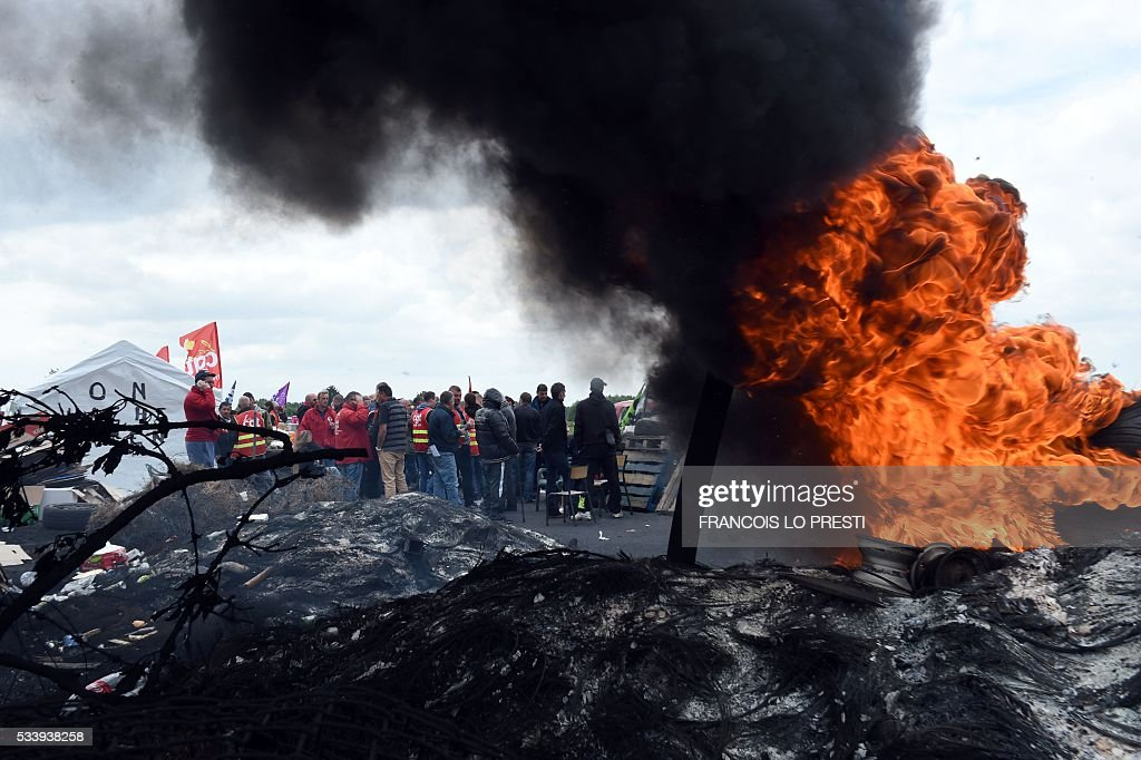French union and sydicates members burn tires as they protest against the proposed government labour reforms as they protest outside a petrol depot at Douchy-Les-Mines, northern France on May 24, 2016. France's government stepped up efforts to break blockades and strikes at refineries that are threatening to paralyse the country just three weeks ahead of the Euro 2016 football tournament. Six out of eight of the refineries in France have either stopped operating or have reduced output due to strikes and blockades. / AFP / FRANCOIS