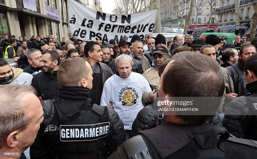 French union CGT representative Jean-Pierre Mercier (C) faces gendarmes next to employees of French auto giant PSA Peugeot Citroen Aulnay gathering outside France's MEDEF employers' association headquarters on March 28, 2013 in Paris, to protest against the planned closure of their plant. Banner on the background reads 'No to the closure of PSA Aulnay'.