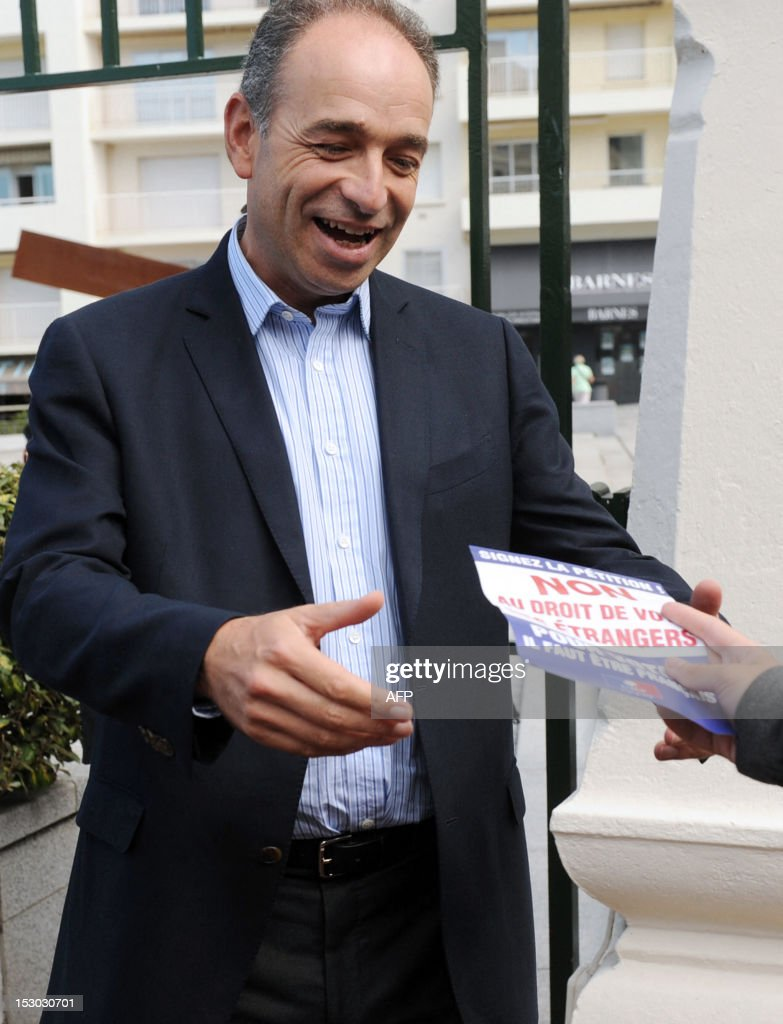 French Union for a Popular Movement (UMP) right-wing opposition party's General Secretary, Jean-Francois Cope, candidate to take over the leadership of UMP, is delivered a leaflet about a petition against the right of non-European foreigners to vote in France, as he arrives to give a meeting on September 29, 2012, in Biarritz, southwestern France, as part of the campaign for the November 18th internal vote.