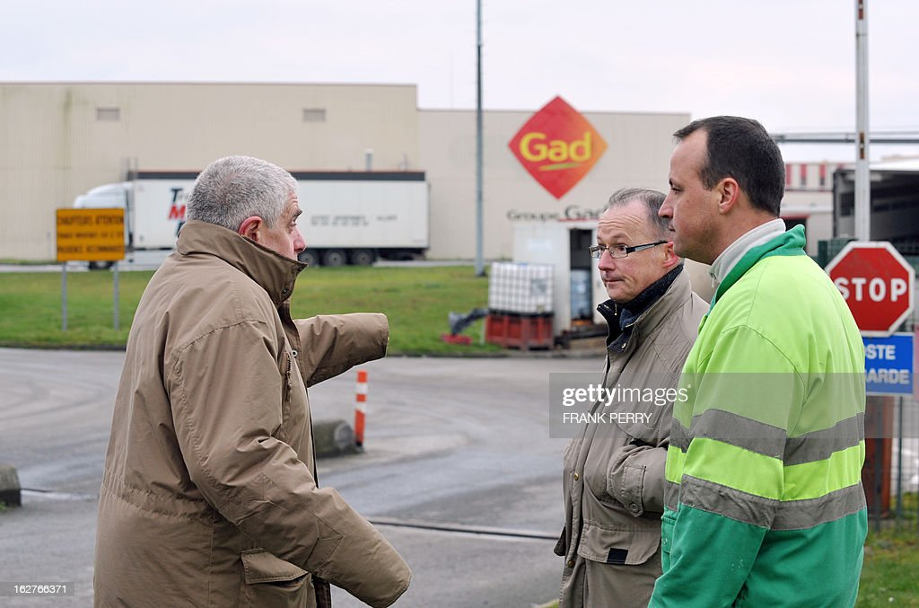 French unions representatives speak together in front of the Gad pig-slaughtering plant in Josselin, western France, on February 26, 2013, following the volontary liquidation by Agribusiness Group Gad last week. Gad which employs 1,500 workers in two sites, Josselin and Lampaul-Guimiliau, lost 20 million euro (26,15 million US dollars) in 2012. AFP PHOTO FRANK PERRY
