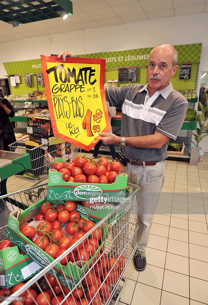 A French vegetable producer holds a sign advertising imported tomatoes during a protest against the sale of vegetables of foreign origin in a Dia discount store in Sainte-Luce-sur-Loire on September 6, 2013.