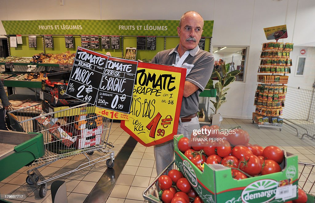 A French vegetable producer holds signs advertising tomatoes imported from other countries during a protest against the sale of vegetables of foreign origin in a Dia discount store in Sainte-Luce-sur-Loire on September 6, 2013. AFP PHOTO/FRANK PERRY