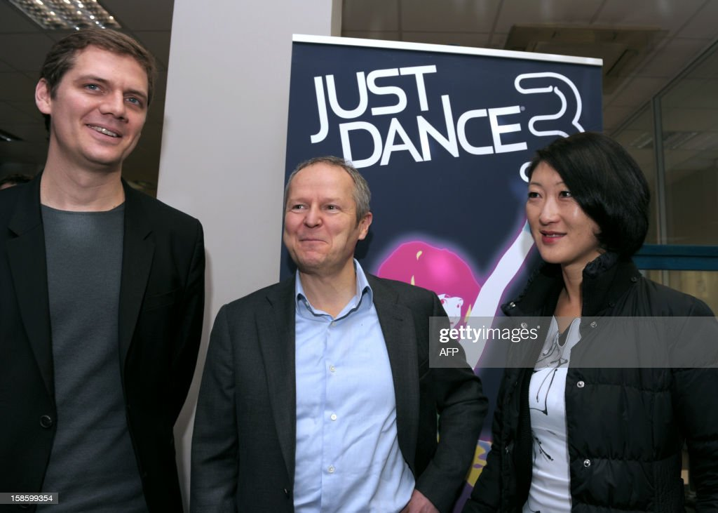 French videogame firm Ubisoft CEO, Yves Guillemot (C) and Xavier Poix (L), head of Ubisoft's studio in France greet French Junior Minister for SMEs, Innovations and Digital Economy, Fleur Pellerin during her visit to Ubisoft's development studio on December 20, 2012 in Montreuil, a Paris' suburb. The poster in the background advertises the Ubisoft's 'Just Dance 3' video game.