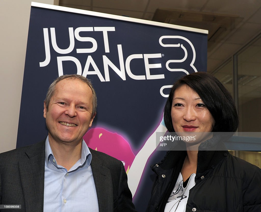 French videogame firm Ubisoft CEO, Yves Guillemot (L) greets French Junior Minister for SMEs, Innovations and Digital Economy, Fleur Pellerin during her visit to Ubisoft's development studio on December 20, 2012 in Montreuil, a Paris' suburb. The poster in the background advertises the Ubisoft's 'Just Dance 3' video game.