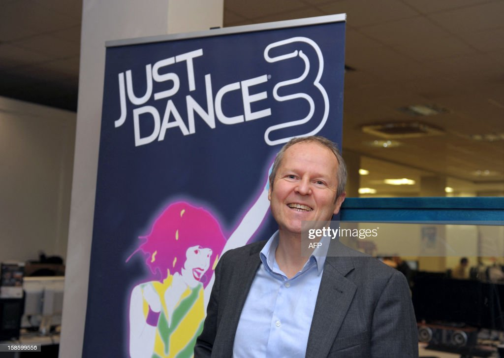 French videogame firm Ubisoft CEO, Yves Guillemot poses in front of the Ubisoft's 'Just Dance 3' video game, prior to a visit by French Junior Minister for SMEs, Innovations and Digital Economy, at Ubisoft's development studio on December 20, 2012 in Montreuil, a Paris' suburb. AFP PHOTO / ERIC PIERMONT