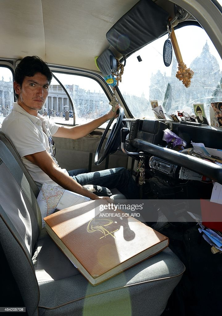 French Vincent Gelot, 26, poses is his 4L car on St. Peter's square, on August 26, 2014 at the Vatican. Vincent Gelot spent the past two years traveling around the world, visiting Christian communities in 23 countries and saving their testimonies in a large leather book which ends with a dedication by the Pope who wrote 'Thank you so much for this testimony of the Eastern Church, a church that has given so many saints and now suffer. I pray for you all, I am close to you.'