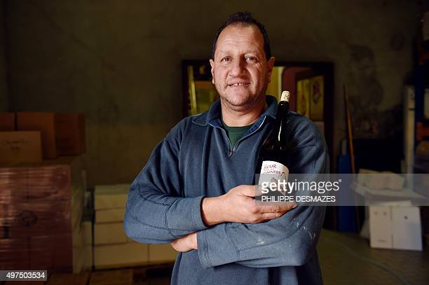 French vineyard owner and wine producer Karim Vionnet poses in VillieMorgon central eastern France on November 10 2015 with a bottle of his new...