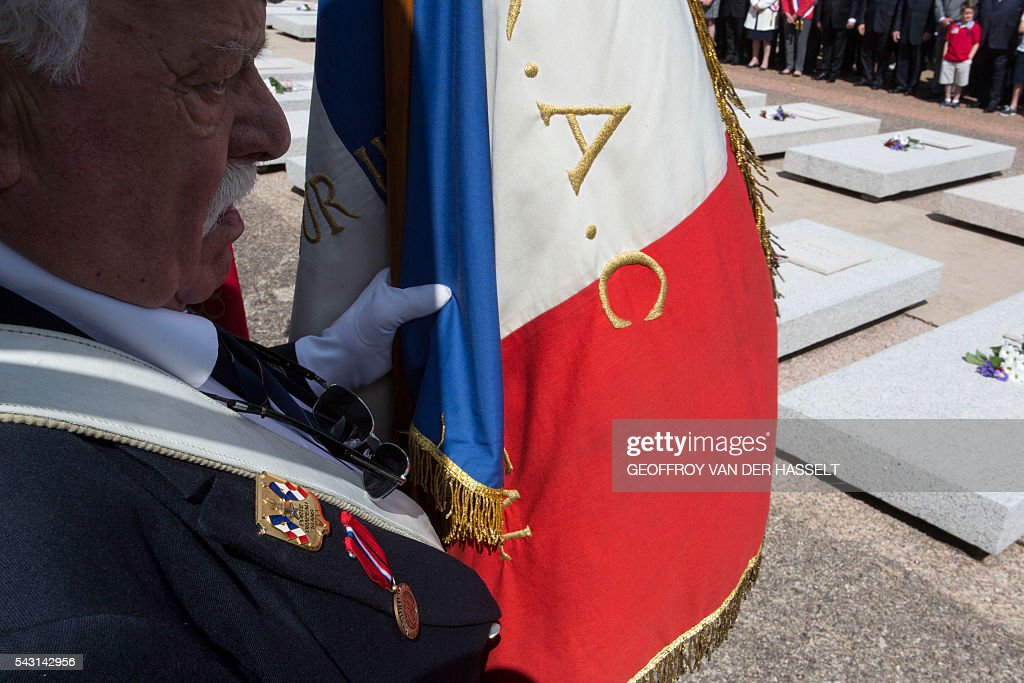 French war veteran stands guard as he hold the French national flag in the cemetery during the inauguration ceremony of the memorial of Dun-les-Places in tribute of the victims killed during the Second World War in Dun-les-Places on June 26, 2016. / AFP / GEOFFROY