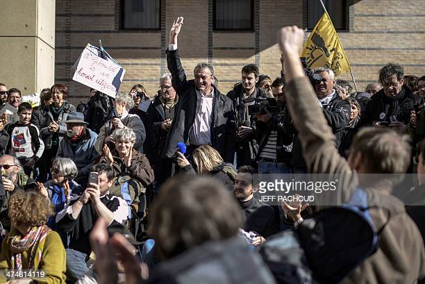 French winemaker Emmanuel Giboulot waves to supporters before entering the court on February 24 2014 in Dijon eastern France Giboulot is pursued by...