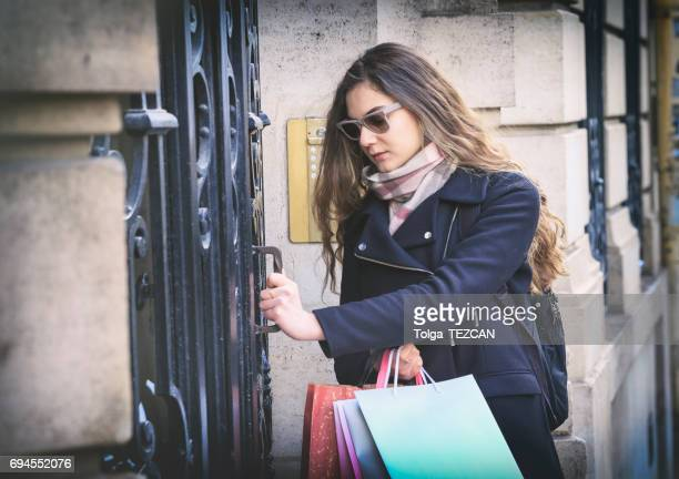 French woman arriving home with a shopping bag
