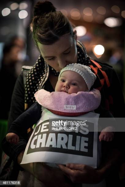 A French woman kisses her baby as she attends a vigil in solidarity with the victims of the shooting at the Paris office of the satirical newspaper...