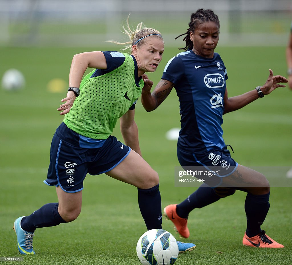 French women's national football team defender Julie Soyer (L) vies with forward Elodie Thomis during a training session on June 20, 2013 in Clairefontaine-en-Yvelines, outside Paris, ahead of the July 10 to 28 European Championship in Sweden. AFP PHOTO / FRANCK FIFE