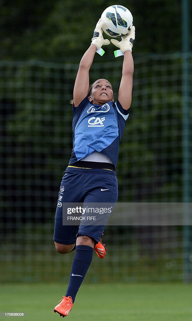 French women's national football team goalkeeper Sarah Bouhaddi jumps for the ball during a training session on June 20, 2013 in Clairefontaine-en-Yvelines, outside Paris, ahead of the July 10 to 28 European Championship in Sweden. AFP PHOTO / FRANCK FIFE