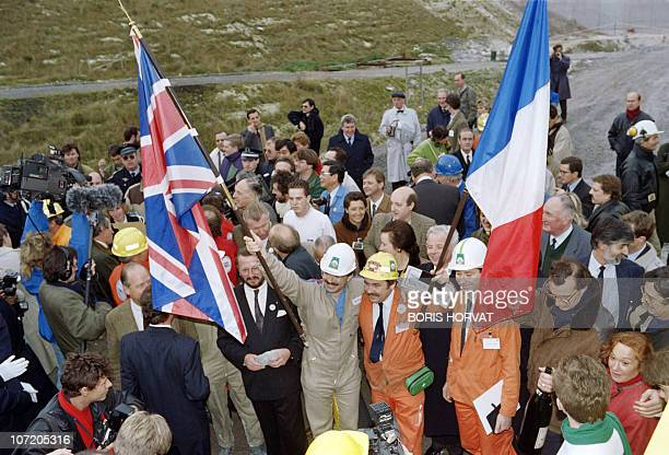 A French worker and his British counterpart hold their national flags on December 1 1990 during the historic breakthrough in the Channel Tunnel AFP...