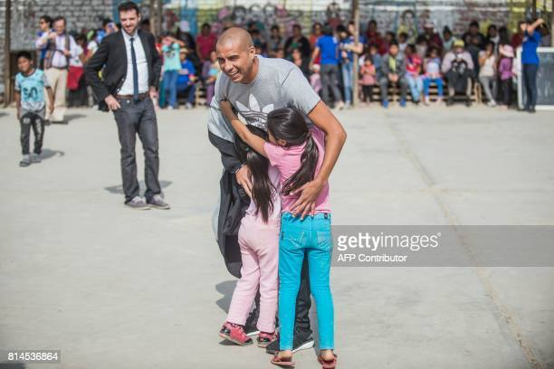 French world football champion David Trezeguet hugs two little girls at San Pablo Mirador community Chancay district in the outskirts of Lima during...