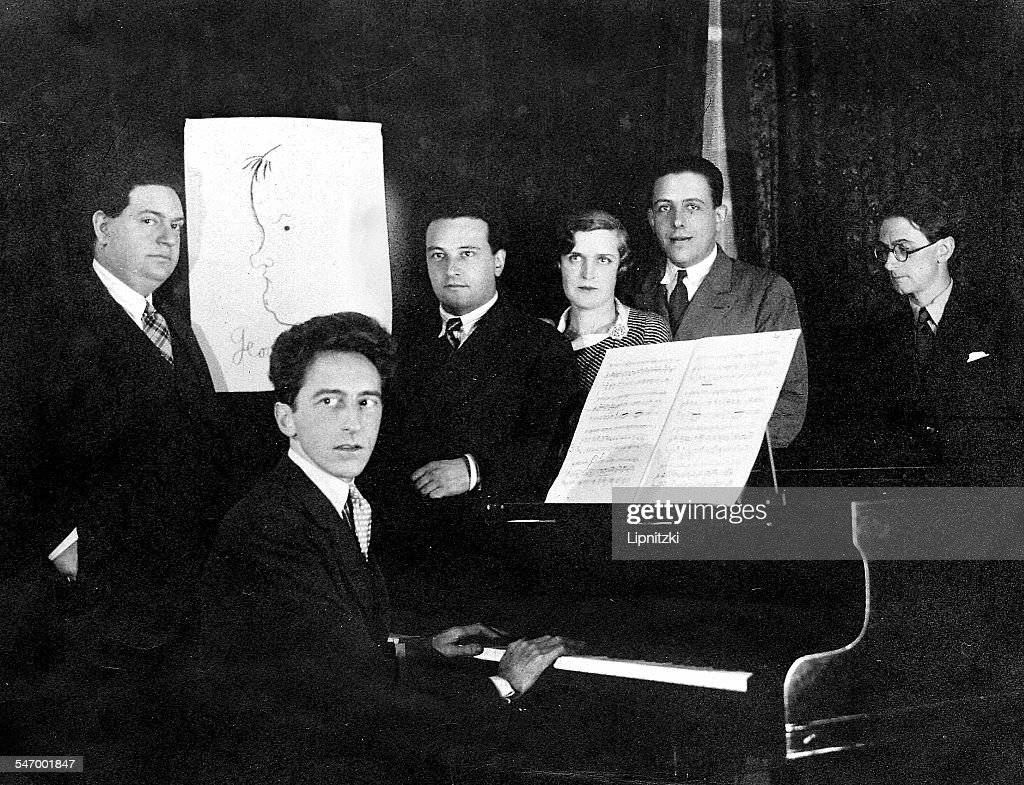 French writer, artist and filmmaker, Jean Cocteau (1889 - 1963 at piano) with five members of the group of French composers known as 'Les Six' ('The Group of six'), 1931. Left to right: Darius Milhaud (1892 - 1974), Cocteau , Arthur Honegger (1892 - 1955), Germaine Tailleferre (1892 - 1983), Francis Poulenc (1899 - 1963) and Louis Durey (1888 - 1979). A portrait by Cocteau (left) stands in for the missing member of Les Six, Georges Auric (1899 - 1983). (Photo by Boris Lipnitzki/Roger Viollet/Getty Images)Darius Milhaud;Arthur Honegger;Germaine Tailleferre;Francis Poulenc;Louis Durey