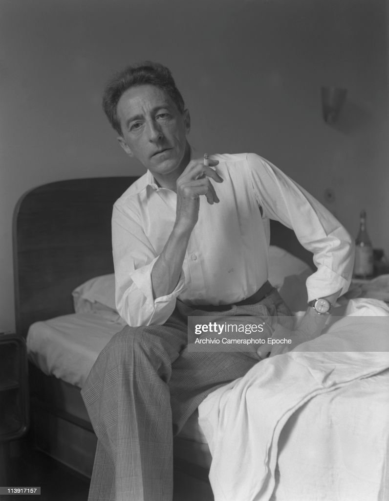 French writer <a gi-track='captionPersonalityLinkClicked' href=/galleries/search?phrase=Jean+Cocteau&family=editorial&specificpeople=211437 ng-click='$event.stopPropagation()'>Jean Cocteau</a> portrayed, sitting on his bed, smoking a cigarette, wearing a white ciphered shirt and plaid trousers, Paris, 1947.
