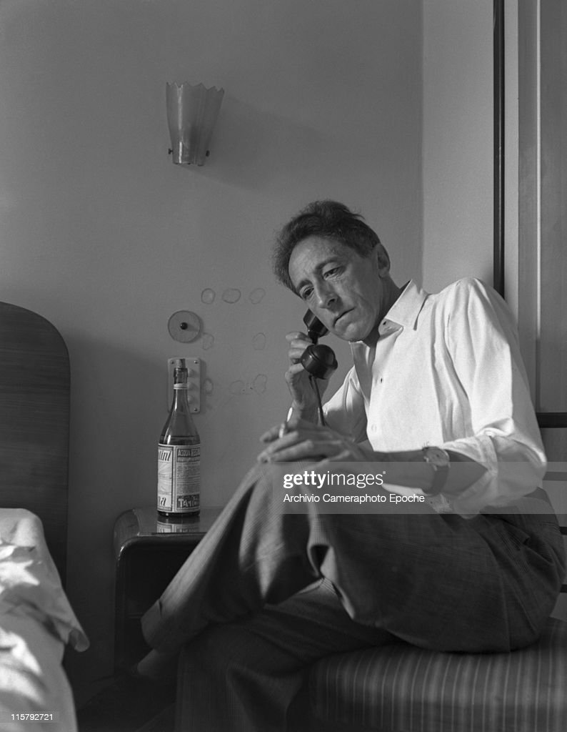 French writer <a gi-track='captionPersonalityLinkClicked' href=/galleries/search?phrase=Jean+Cocteau&family=editorial&specificpeople=211437 ng-click='$event.stopPropagation()'>Jean Cocteau</a> portrayed while sitting on his bed, smoking a cigarette, wearing a white ciphered shirt and plaid trousers, talking on the telephone, a bottle of water on the night table, Paris, 1947.