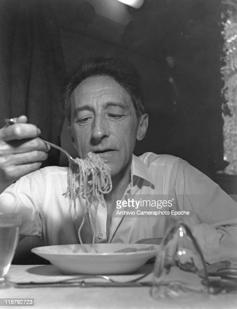 French writer Jean Cocteau sitting at a set table portrayed while eating a dish of spaghetti Venice 1947