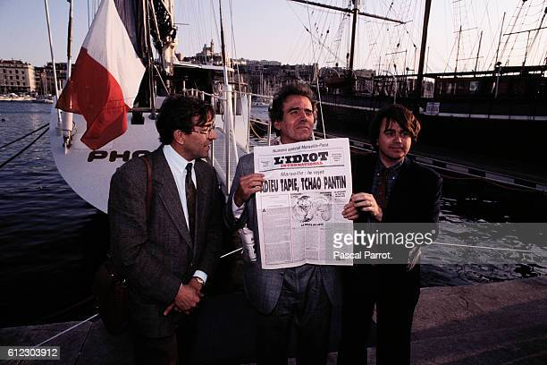 French writer JeanEdern Hallier and lawyers Antoine Gaudino and Gilbert Collard distribute copies of the International Idiot in front of businessman...