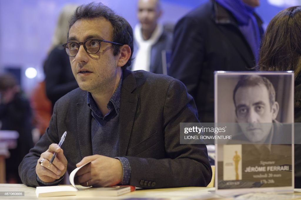 French writer Jerome Ferrari is pictured during an autograph session at the Paris Book Fair on March 20, 2015. AFP PHOTO / LIONEL BONAVENTURE