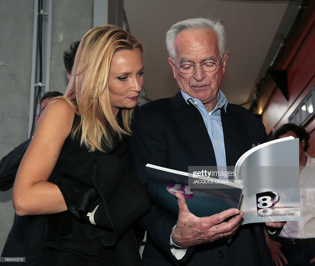 French writer, journalist, radio and TV host Philippe Labro (R) reads a booklet beside French TV host Adrienne de Malleray, on September 20, 2012 in Paris, during the official presentation of the French TV channels D8 (formerly Direct 8 on the digital terrestrial television network) and D17 (formerly Direct Star) led by French media group Canal+. The French television and radio control council (CSA) authorized Canal+, on September 18, to buy out both television channels, which were formerly owned by French businessman Vincent Bollore.