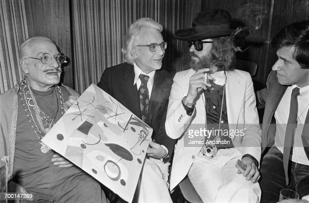 French writer Roger Peyrefitte holding a copy of a painting as he talks to FrenchAmerican art dealer Fernand Legros on the set of the Antenne 2 TV...