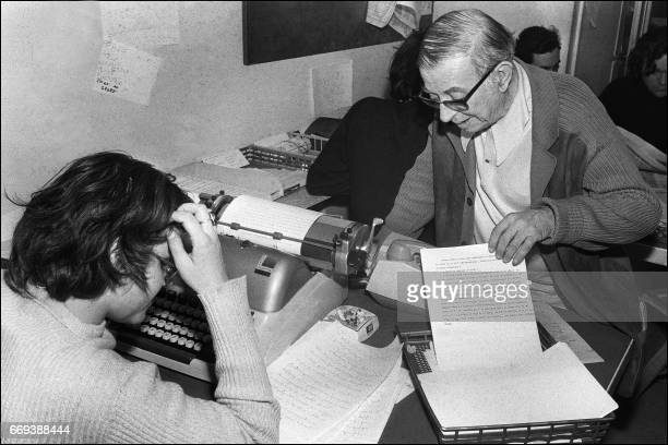 French writers JeanPaul Sartre first editorial director of 'Liberation' is seen on March 5 1973 working next to a journalist in the news room of the...