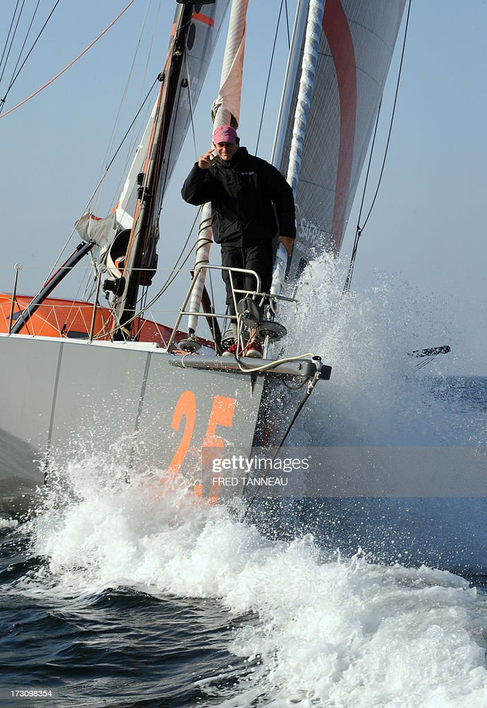 French yachtsman Marc Guillemot stands on his 'Safran' monohull as he arrives in La Trinite-sur-Mer, western France, on July 7, 2013 after establishing a new record across the north Atlantic Ocean. Guillemot set a new record for a solo, single-hulled crossing of the north Atlantic Ocean, slicing more than 15 hours off the previous mark. AFP PHOTO / FRED TANNEAU