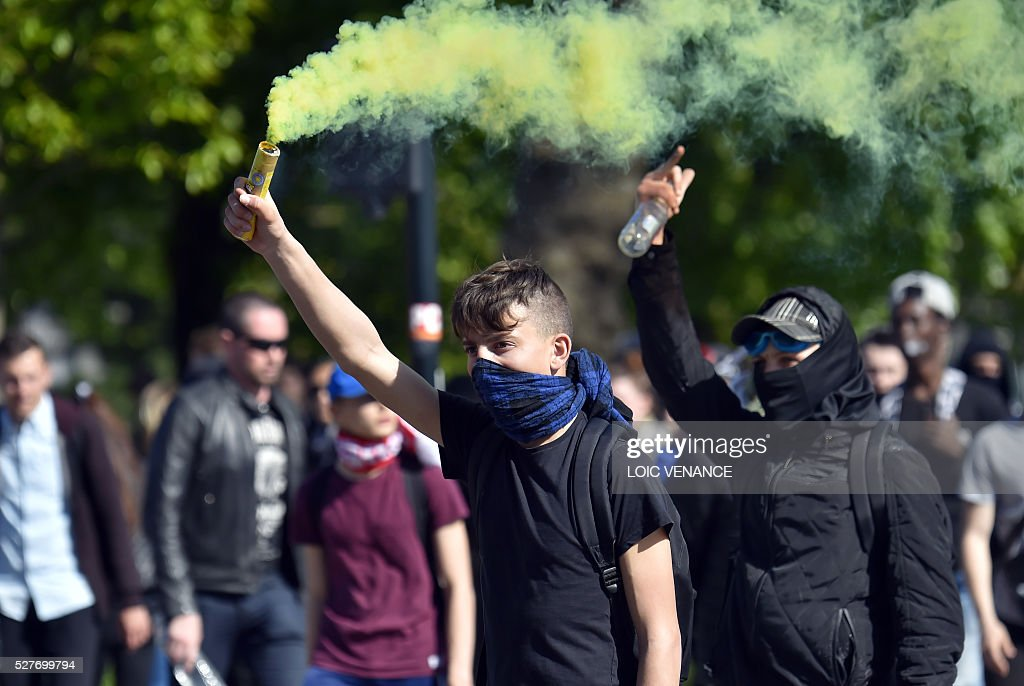 A French youth holds a flare as he takes part in a protest against the government's planned labour law reforms in Nantes, western France, on May 3, 2016. High school pupils and workers protested against deeply unpopular labour reforms that have divided the Socialist government and raised hackles in a country accustomed to iron-clad job security. / AFP / LOIC