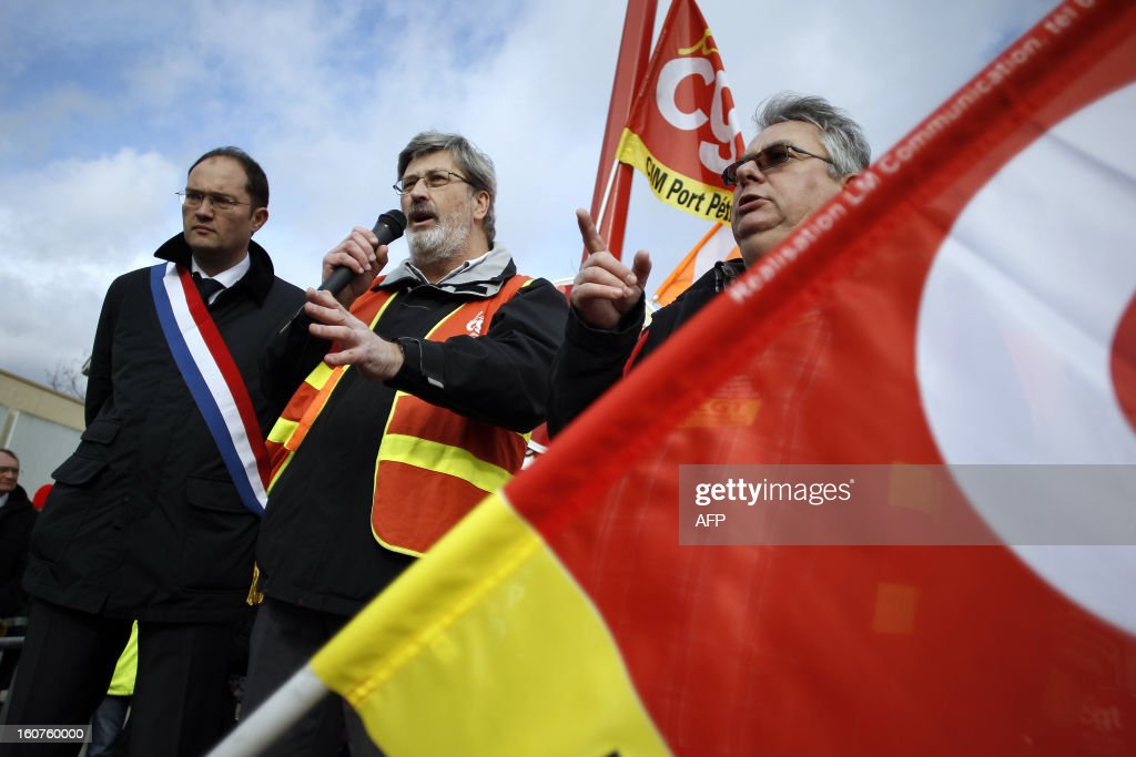 French Yvon Scornet (C), unions' spokeman of the Petroplus oil refinery, talks to Petroplus oil refinery workers, next to French socialist MP Guillaume Bacheley (L), during a protest outside the Petroplus oil refinery, on February 5, 2013 in Petit-Couronne, northwestern France. A French court ordered last October the liquidation of Petit-Couronne oil refinery despite two offers for the site that employs 470 people. Investors have until this evening to make bids for the business, and the Minister for Industrial Regeneration Arnaud Montebourg said on RTL radio early in the day that the government expected several offers.
