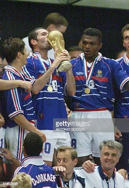 French Zinedine Zidane kisses the FIFA Trophy 12 July at the Stade de France in SaintDenis after the 1998 World Cup final match pitting Brazil...