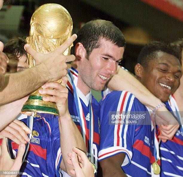POOL French Zinedine Zidane stands next to the FIFA Trophy with teammate Marcel Desailly 12 July at the Stade de France in SaintDenis after the 1998...