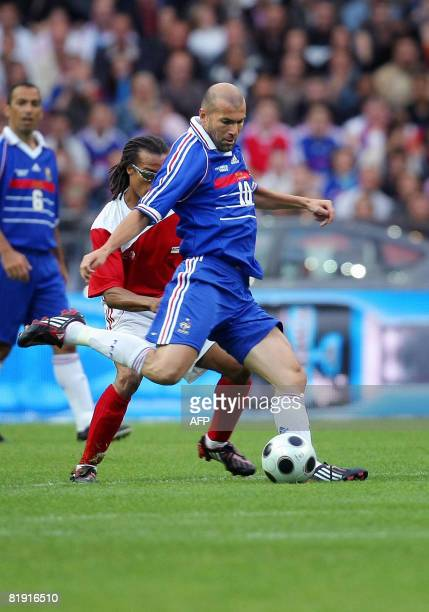 French Zinedine Zidane vies with Dutch Edgar Davids during their football exhibition match between France's 1998 World Cup champions and a world...