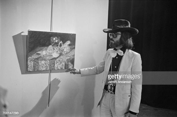 FrenchAmerican art dealer Fernand Legros posing with a copy of a famous painting on the set of the Antenne 2 TV debate show 'Les Dossiers de l'Écran'...