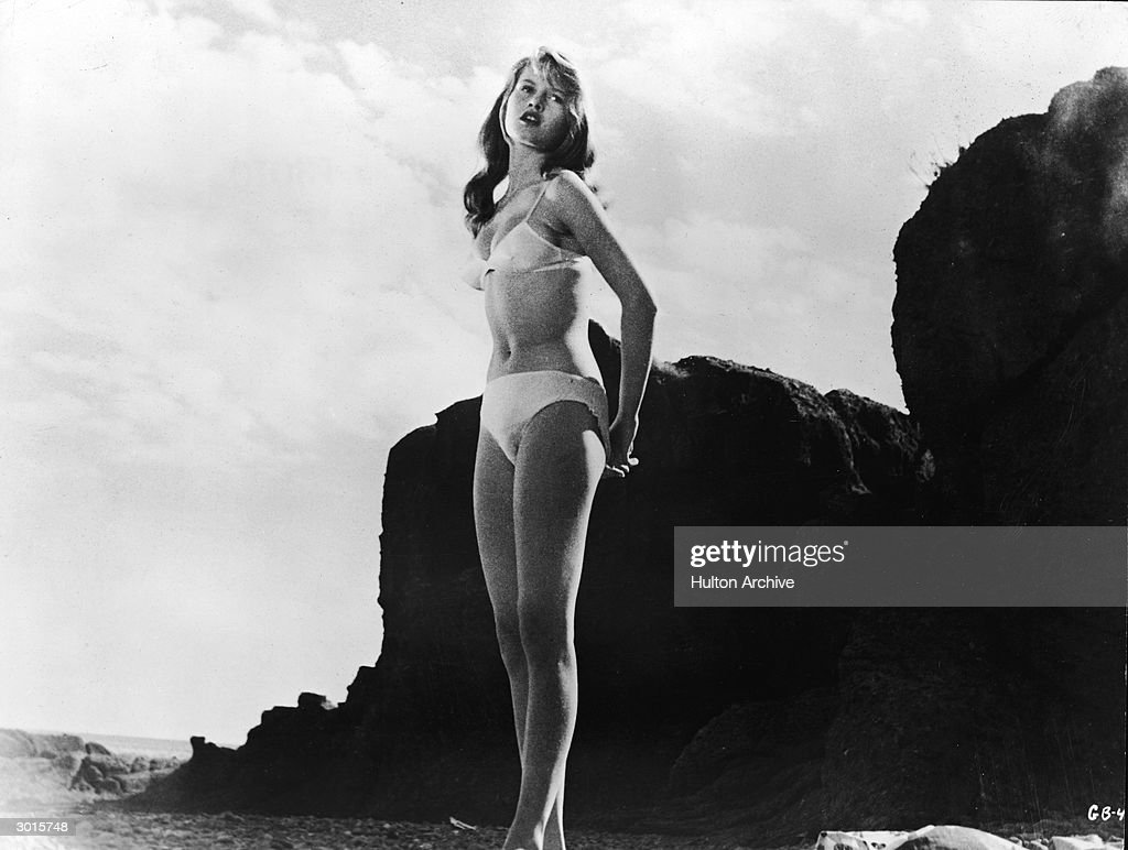 French-born actor <a gi-track='captionPersonalityLinkClicked' href=/galleries/search?phrase=Brigitte+Bardot&family=editorial&specificpeople=202903 ng-click='$event.stopPropagation()'>Brigitte Bardot</a> wears a white bikini and stands on a rocky beach in a still from the film, 'The Girl in the Bikini', directed by Willy Rozier, 1958.