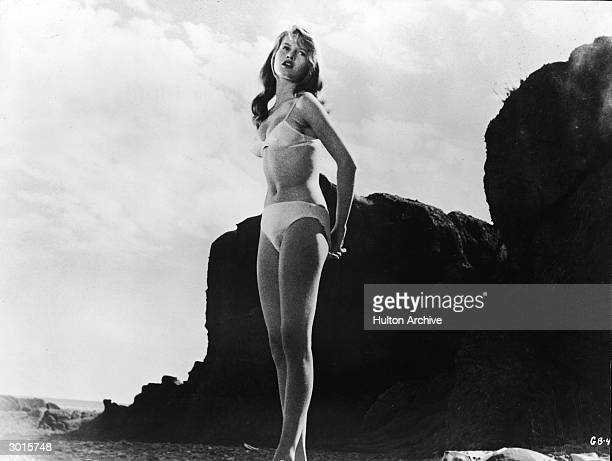 Frenchborn actor Brigitte Bardot wears a white bikini and stands on a rocky beach in a still from the film 'The Girl in the Bikini' directed by Willy...