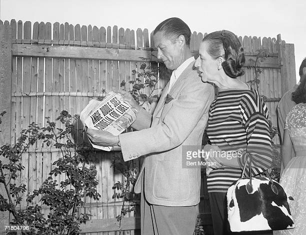 Frenchborn American fashion editor Diana Vreeland and her husband banker Thomas Reed Vreeland stand in a yard near a picket fence and read the front...