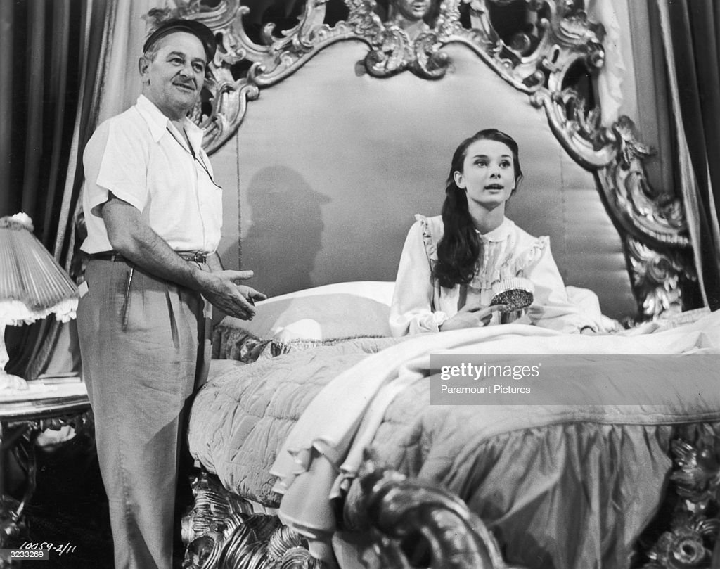 French-born director William Wyler directs Belgian-born actor Audrey Hepburn on the set of his film, 'Roman Holiday'. Hepburn is sitting up in bed and holds a brush.