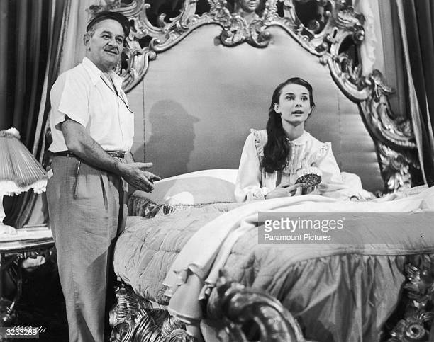 Frenchborn director William Wyler directs Belgianborn actor Audrey Hepburn on the set of his film 'Roman Holiday' Hepburn is sitting up in bed and...